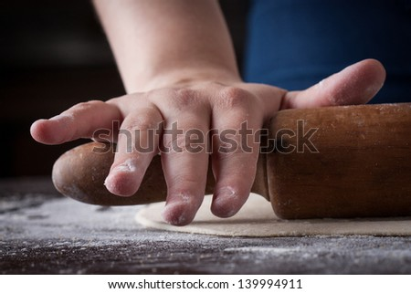 Cook hands preparing pizza dough on a wooden table - stock photo