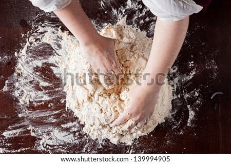 Cook hands preparing pizza dough on a wooden table overhead shot - stock photo