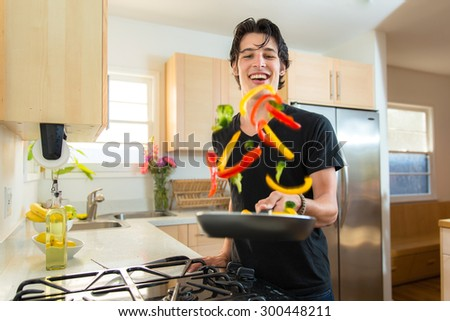 Cook handsome chef man flips tosses veggies on frying pan making dinner - stock photo