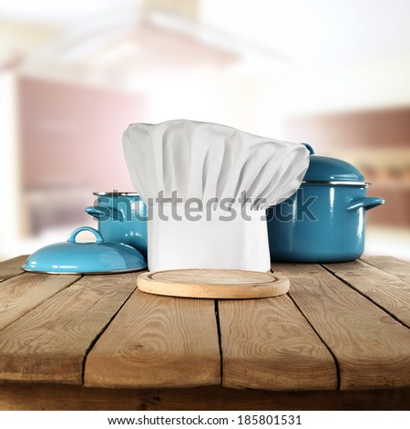 cook hat in kitchen and wooden desk  - stock photo