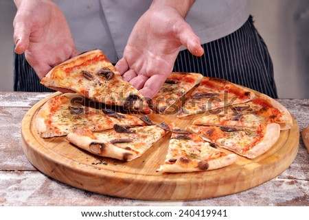 Cook holding a pizza slice. - stock photo