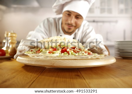 cook in kitchen and white clothes with white big hat