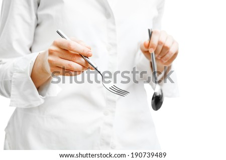 cook in snow white uniform holding a fork in hand  - stock photo