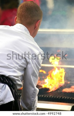 cook in white suit preparing barbecue - stock photo
