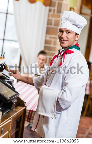 cook inserts the card into a computer terminal, against visiting the restaurant - stock photo