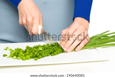 Cook is chopping green onion, closeup shoot, isolated over white - stock photo