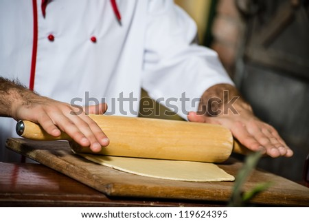 cook man rolls the dough with a rolling pin, for pizzas - stock photo