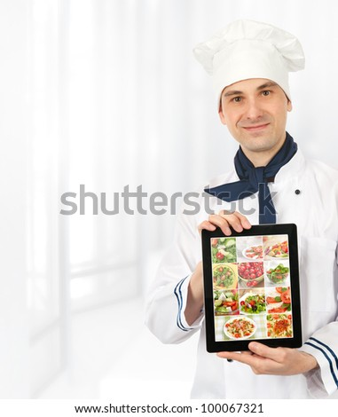 cook man showing a digital tablet with menu - stock photo