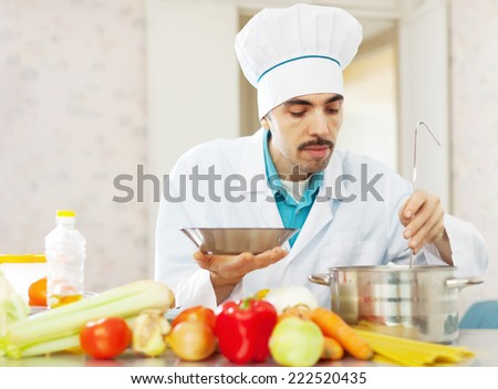cook man  tasting soup with ladle from pan in kitchen - stock photo