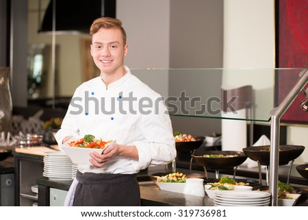 cook or chef from catering service posing with food in front of buffet - stock photo