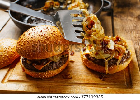 Cook placing fryed oning on burger - stock photo