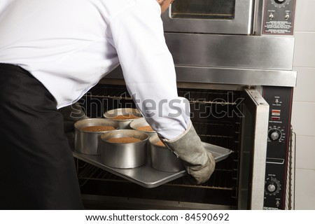 Cook placing the cakes in the oven