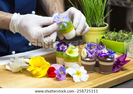 cook prepares canapes dessert edible flowers and buds - stock photo