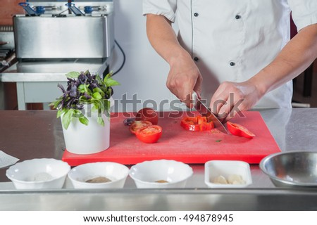 cook prepares in the kitchen Close-up of a hand cutting vegetables