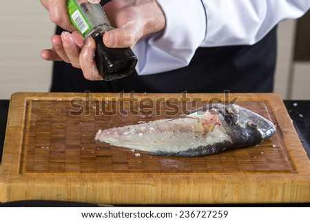 Cook preparing sea bream fish at restaurant - stock photo