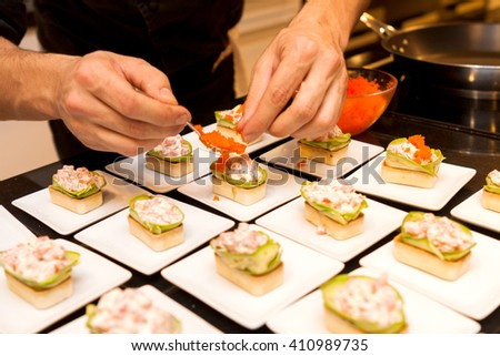 cook put red caviar on prepared delicious gourmet canape starters on white plates - stock photo
