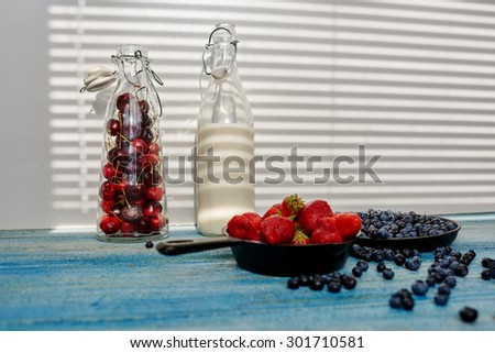 Cook resigned berries in a pan to cook one delicious mincemeat, there are a number of glass bottles of wine in the buyout sprinkling berries - stock photo