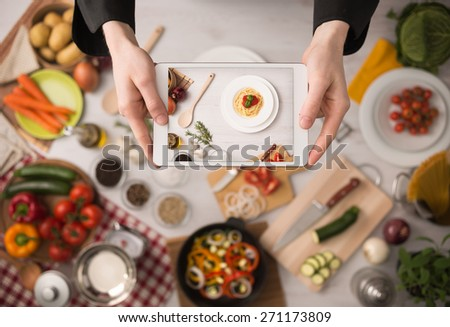 Cook's hands holding a touch screen tablet close up, kitchen table with food ingredients, vegetables and utensils on background, top view - stock photo