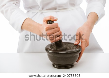 Cook's hands pounding something using mortar and pestle, closeup shot - stock photo