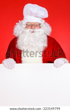 Cook Santa Claus with white message board - stock photo