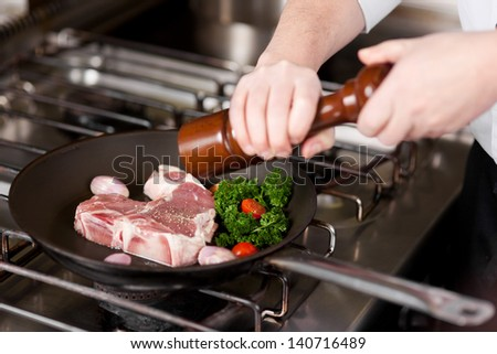 cook seasoning meat with pepper from a pepper mill