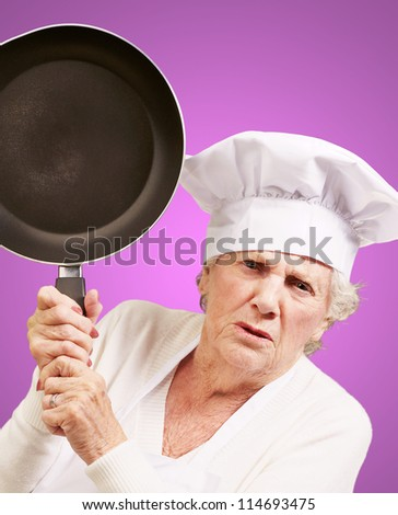 Cook senior woman angry trying to hit with pan over purple background - stock photo