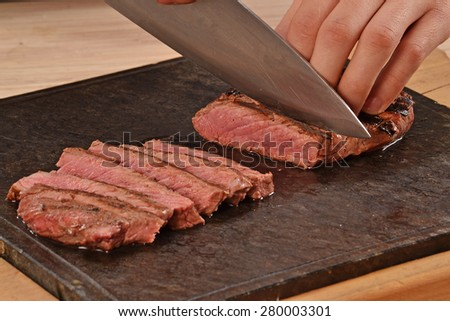 Cook slicing grilled beef steak on stone board. - stock photo