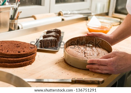 Cook taking out layer cake from cake form - stock photo