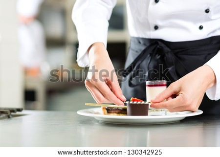 Cook, the female pastry chef, in hotel or restaurant kitchen cooking, she is finishing a sweet dessert