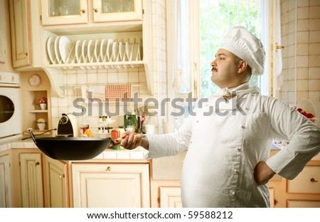 Cook using a pan in a kitchen - stock photo