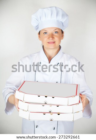 cook with a pizza in the box on a light background - stock photo