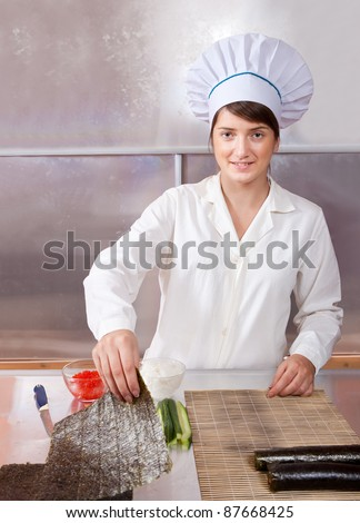 Cook woman making  japanese sushi rolls in kitchen - stock photo