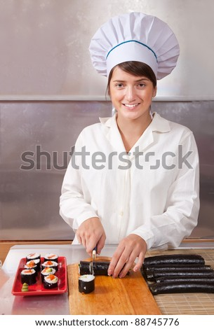 Cook woman making  japanese sushi rolls in kitchen