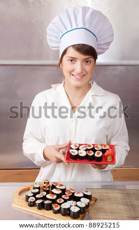 Cook woman with cooked  sushi rolls in kitchen - stock photo