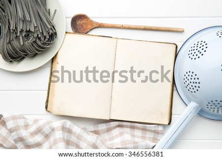 cookbook and black noodles with squid sepia ink on white table - stock photo