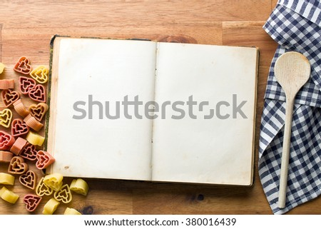 cookbook and heart shaped pasta on wooden table