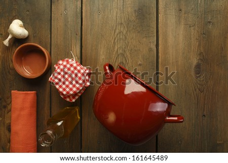 Cookbook background. An old wooden kitchen table. Bottle of olive oil, garlic, jar, saucepan, pot, bowl and dishtowel/Bottle of olive oil, garlic, jar and pot on picnic table - stock photo
