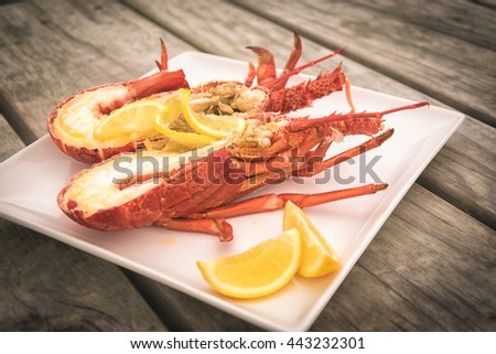 Cooked and halved New zealand cray dish on th wooden table. - stock photo