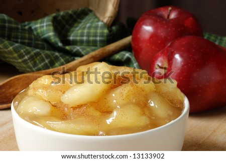 Cooked apples sprinkled with cinnamon.  Basket with green fabric, vintage wooden spoon and apples in the background.  Close-up with shallow dof. - stock photo