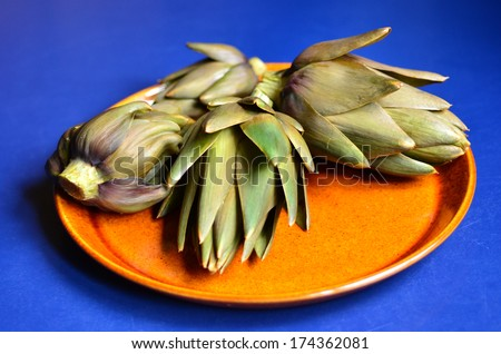 Cooked Artichoke served on a plate. - stock photo
