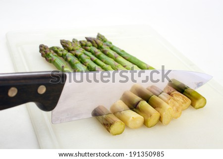 Cooked asparagus , cutting off stalk ends with kitchen knife - stock photo