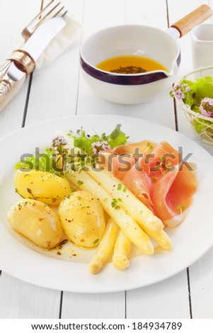 Cooked asparagus spears with Italian prosciutto ham and boiled baby potatoes served with an olive oil and herb dressing on a white wooden counter in a country kitchen - stock photo