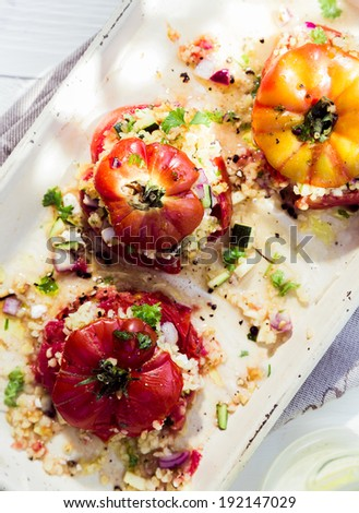 Cooked baked tomatoes with fresh herbs and savory grain stuffing on a platter for a tasty nutritious, appetizer or accompaniment to a meal - stock photo