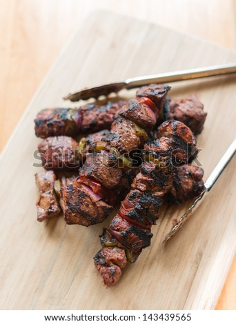 Cooked beef meat kebab on a wooden board. Very shallow depth of field. - stock photo