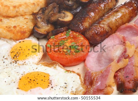 Cooked breakfast with bacon, sausage, eggs, mushrooms and hash browns - stock photo