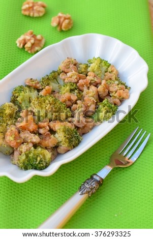 Cooked broccoli with walnut as side dish