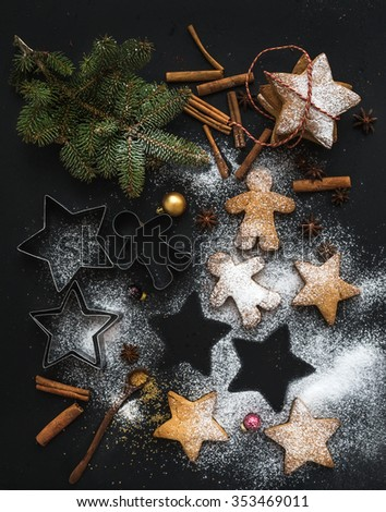 Cooked Christmas holiday traditional gingerbread cookies with sugar powder and cinnamon sticks on black background, top view - stock photo