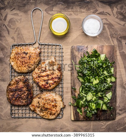 cooked, delicious grilled pork steak with green salad of cucumber, spinach and arugula on wooden rustic background top view close up - stock photo