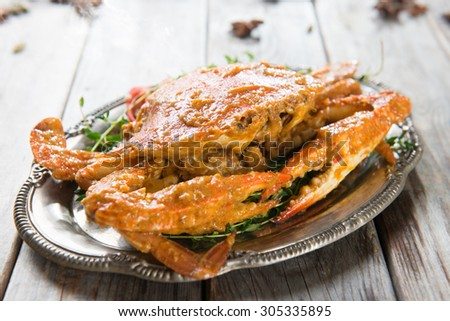 Cooked delicious hot and spicy sauce blue crab, on wooden background. Fresh cook with hot smoke steams. - stock photo