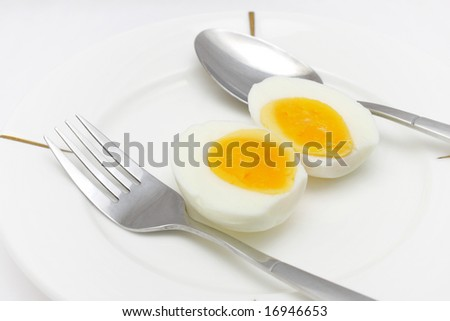 Cooked egg put on white plate with folk and spoon.